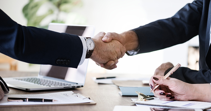Photo of two persons shaking hands.